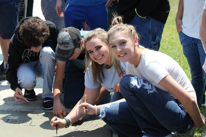 seniors smile as they sign the sidewalk.