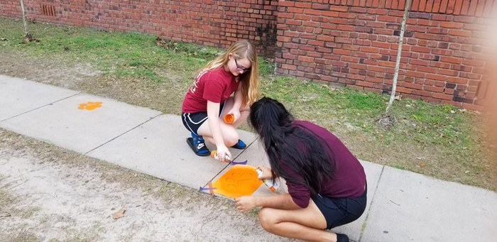 Tri-M paints paw prints around campus.
