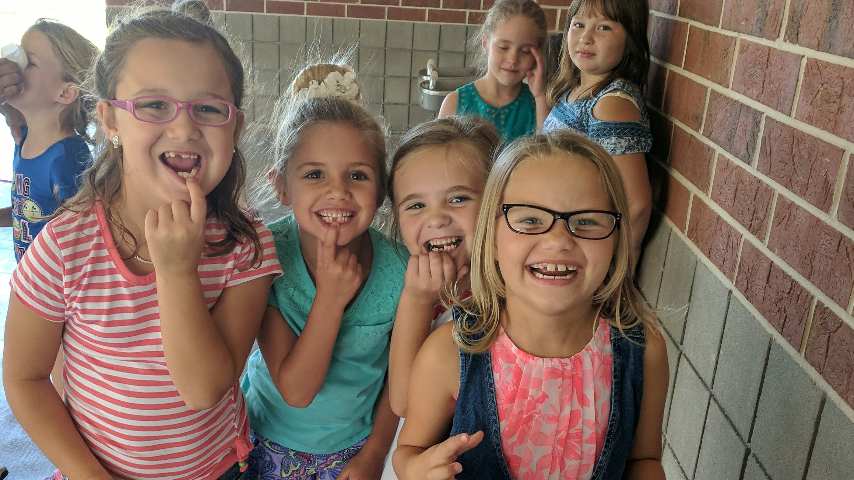 First grade girls showing off their newly missing teeth.